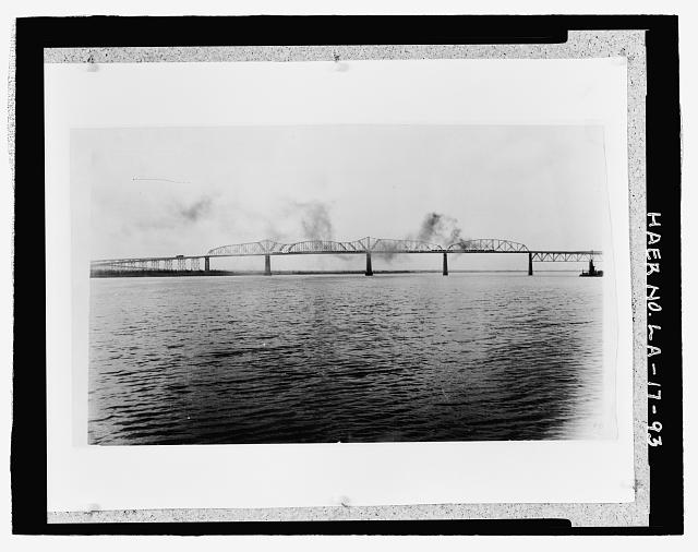 "Photographic copy of early 20"" x 33"", black and white photograph.  Located loose in oversized box at the National Museum of American History, Smithsonian Institution, Archives Center, Work and Industry Division, Washington, D.C.  Original Photographer unknown. EARLY PHOTOGRAPH OF BRIDGE TAKEN FROM DOWN RIVER NEAR EAST BANK LOOKING SOUTHWEST UP RIVER TOWARD WEST BANK SHOWING STEAM LOCOMOTIVE TRAIN CROSSING BRIDGE. - Huey P. Long Bridge, Spanning Mississippi River approximately midway between nine & twelve mile points upstream from & west of New Orleans, Jefferson, Jefferson Parish, LA"