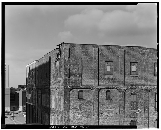 11.  SOUTH AND EAST SIDE, THREE-QUARTER VIEW, DETAIL SHOWING SIXTH-FLOOR BRICK ADDITION AND ORIGINAL BRICK PILASTERS; LOOKING NORTHWEST - Crown Roller Mill, 105 Fifth Avenue, South, West Side Milling District, Minneapolis, Hennepin County, MN