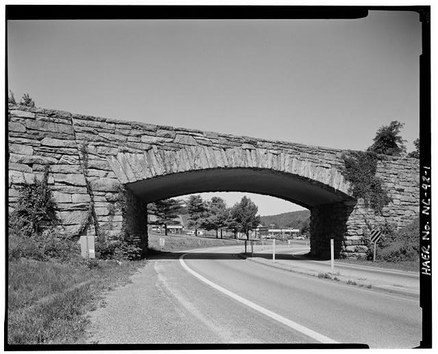 1.  U.S. Route 250 grade separation structure. This reinforced concrete, rigid frame structure was built in 1941. Its relatively flat arch provided maximum useful clearance in a short span and the physics of the design eliminated the need for extensive abutments to contain the thrust of traditional arches, making it ideally suited as a grade separation structure.  BLRI designers made extensive use of theses bridges for crossing small streams and creeks, and grade separation structures, ornamenting them with a rustic stone facade. View is of the south-southeast elevation. - Blue Ridge Parkway, Between Shenandoah National Park & Great Smoky Mountains, Asheville, Buncombe County, NC