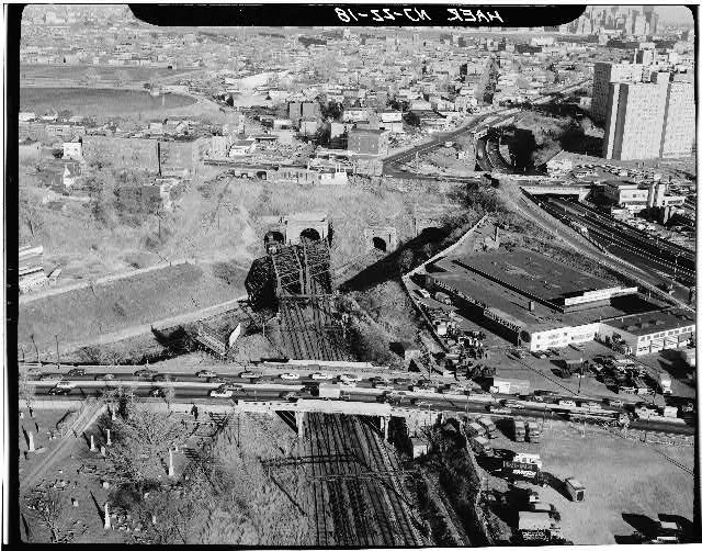 18.  1978 aerial view to east of west ends of Bergen Hill tunnels. Tunnel openings from right to left: Bergen Hill Open Cut (Erie Ry.), Old Bergen Hill Tunnel (Erie Ry.), two tunnels built by Delaware, Lackawanna & Western Railroad (later Erie-Lackawanna Railroad). Photo by Jack E. Boucher, 1978. - Erie Railway, Bergen Hill Open Cut, Palisade Avenue to Tonnele Avenue, Jersey City, Hudson County, NJ