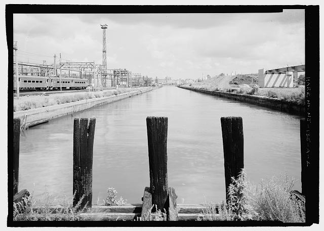 View east, view of full length of canal, west wall pileheads in foreground. - Delaware, Lackawanna & Western Railroad Freight & Rail Yard, Long Slip Canal, New Jersey Transit Hoboken Rail Yard, Hoboken, Hudson County, NJ