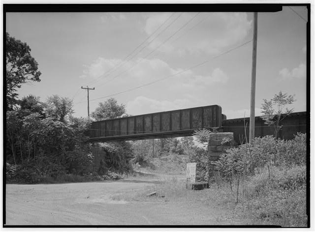 Half-through girder over entrance to scrap yard at western end of trestle, looking NW. - Pennsylvania Railroad, French Creek Trestle, Spanning French Creek, north of Paradise Street, Phoenixville, Chester County, PA