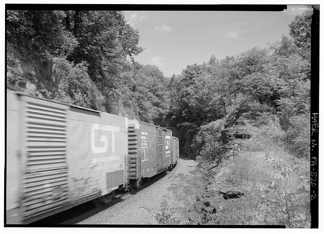 Cut at eastern approach, with portal obscured by train entering tunnel, looking NNW. - Philadelphia & Reading Railroad, Black Rock Tunnel, Beneath Black Rock Hill, southwest of Black Rock Dam, Phoenixville, Chester County, PA