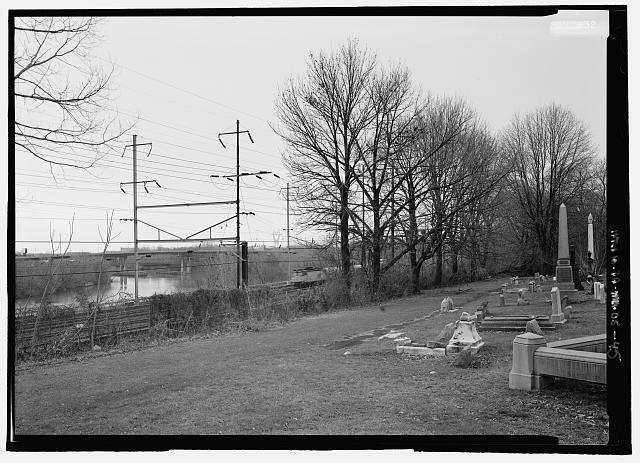 VIEW OF THE RAILROAD TRACKS AND SCHUYLKILL RIVER,  LOOKING SOUTH FROM SECTION L. THE WOODLANDS TRACT ORIGINALLY EXTENDED TO THE RIVER. THIS FRONTAGE WAS SOLD IN 1853 TO THE WEST CHESTER AND PHILADELPHIA RAILROAD AS A RIGHT-OF-WAY FOR A TRACK BED.  THE CORRIDOR HAS SINCE BEEN WIDENED CONSIDERABLY: THREE COMMUTER TRAINS NOW CONVERGE THERE AS DO NATIONAL PASSENGER AND FREIGHT LINES - Woodlands Cemetery, 4000 Woodlands Avenue, Philadelphia, Philadelphia County, PA