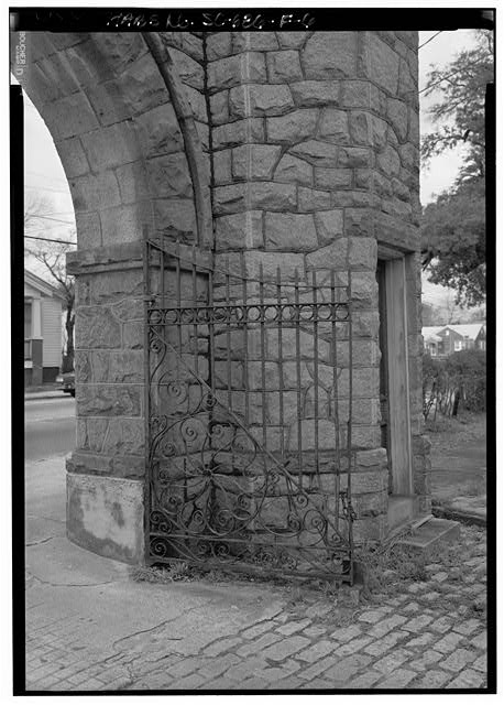 6.  DETAIL VIEW OF ENTRANCE GATES, SHOWING IRON GATE, STONE WORK, AND GATE STOP FROM SOUTHEAST OF NORTHWEST ELEMENTS. - William Enston Home, Entrance Gate, 900 King Street, Charleston, Charleston County, SC