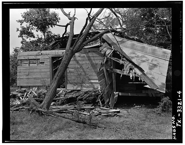 4.  WEST SIDE ELEVATION SHOWING WEATHERBOARD LOG COVERING, DOOR CUT INTO WEST WALL TO ENTER DOG TROT, AND UPROOTED TREE WHERE LATER SECOND PEN WAS LOCATED (4 x 5 negative) - Thomas Jefferson Walling Log Cabin, Henderson, Rusk County, TX