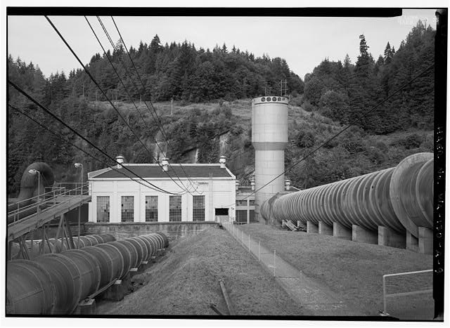 VIEW OF  PENSTOCK AND SURGE TANK LEADING INTO SOUTH SIDE OF ELWHA POWERHOUSE.  PHOTO BY JET LOWE, HAER, 1995. - Elwha River Hydroelectric System, Elwha Hydroelectric Dam & Plant, Port Angeles, Clallam County, WA