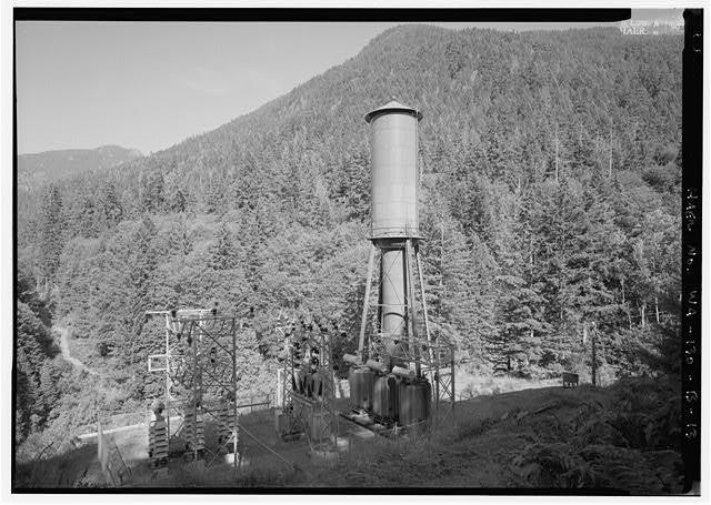 VIEW OF SURGE TANK AND TRANSFORMER YARD FROM HILL ABOVE POWERHOUSE.  PHOTO BY JET LOWE, HAER, 1995. - Elwha River Hydroelectric System, Glines Hydroelectric Dam & Plant, Port Angeles, Clallam County, WA