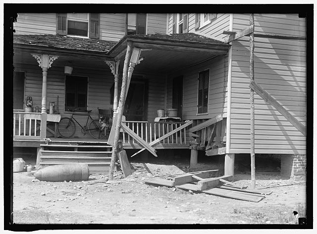 INDIAN HEAD, MD. NAVY PROVING GROUND. RESIDENCE OF GEORGE SWANN, DAMAGED BY 16&#39; SHELL THAT HIT ANOTHER IN SANDBANK, AND WAS DEFLECTED OVER COUNTRY AT 3/4 ANGLE. THE SHELL, WHERE IT STOPPED IN DOORYARD