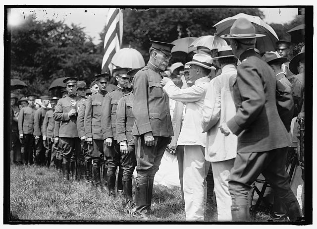 HARVEY, WILLIAM E. COLONEL, N. A. BEING DECORATED BY SEC. BAKER