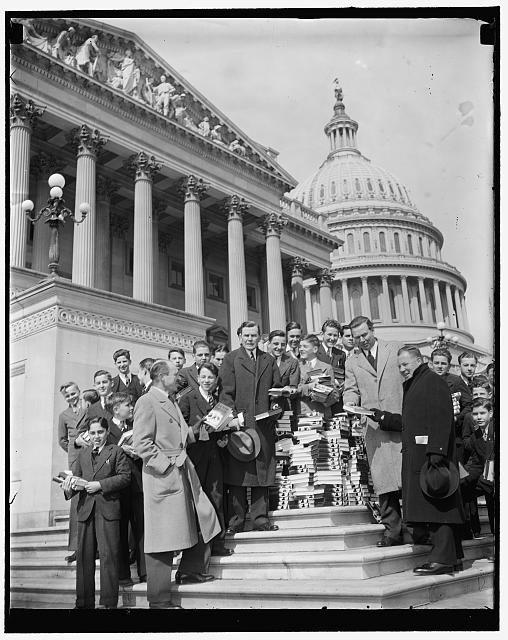 [Group with stack of books on steps of U.S. Capitol]