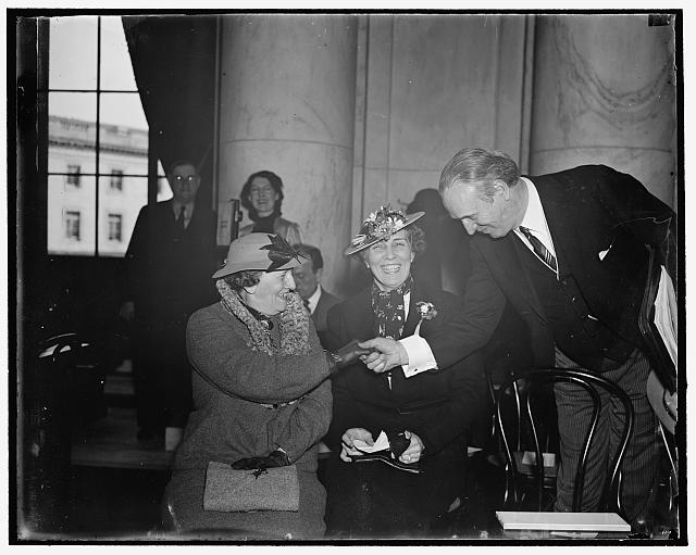 "Welcome ladies! Washington, D.C., March 19. The open hearing being by the Senate Judiciary Committee on the President's proposed Supreme Court plan is proving the ""hit"" of the present congressional session, at least by the members of the fair sex. Here we see Senator Henry F. Ashurst, Chairman of the Committee, greeting Mrs. Joseph E. Davies, former wife of the American Ambassador to the Soviet, and her daughter Mrs. Millard Tydings, wife of the Maryland Senator, as they arrived to attend today's session, 3/19/1937"