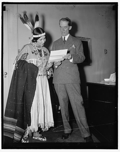 Indian Princess invites President Grand Council Washington D.C. June 28. Dressed in full regalia, Princess White Deer, extended an invitation to President Roosevelt at the White House today to attend the Six Nations Iroquis Grand Indian Council July 5 at St. Regis Reservation. The Princess; who is shown with Presidential Secretary Marvin H. McIntyre said the Indian powwow will be the first time Iroquis Indians have held their council since pre-revolutionary days. 6/28/37