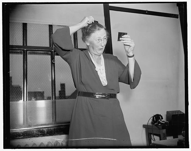 New Social Security board member primps. Washington, D.C., Aug. 23. Cameramen were kept waiting today while Miss Mary Dewson, new member of the social security board, checked her appearance before posing for pictures taking the oath of office, 8/23/37