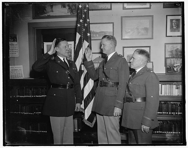 New Chief of Chaplains takes oath. Washington, D.C., Dec. 23. For the first time in the history of the Army a Roman Catholic priest was inducted into office as Chief of U.S. Chaplains. He is Col. William R. Arnold (center) and is shown taking the oath as administered by Maj. Gen. Allen W. Gullion, Judge Advocate General. On the right is Chaplain Alva J. Brasted, whom Col. Arnold succeeds, 12/23/37