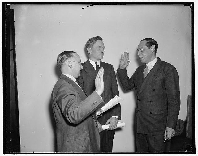 "New SEC member takes oath. Washington, D.C., Dec. 27. Declaring himself to be neither a radical nor a conservative but an enthusiastic ""new dealer"", Jerome N. Frank today took the oath of office as a member of the Securities and Exchange Commission. Frank, a former legal counsel for the WPA and the AAA, succeeds James M. Landis who resigned his post to become Dean of the Harvard Law School. John. W. Hanes, the other new commission appointee, will be sworn in after the first of the year. Left to right: Francis P. Brassor, Secretary of the Commission; Chairman William O. Douglas; and Frank"
