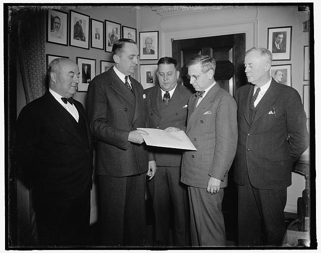 Pan American awarded New York-Bermuda airmail contract. Washington, D.C., Jan. 15. Submitting the only bid, Pan American Airways today was awarded the contract to carry air mail from New York to Hamilton, Bermuda. In announcing the bid the Post Office Department said the following rates would prevail --.00001 cents per pound for a specified load of 800 pounds and .000005 cents per pound over 800 pounds. In the photograph, left to right: William L. Slattery, P.O. Dept. Comptroller; J. Carroll Cone, Atlantic Manager for Pan American; Roy M. North, Acting 3rd Assistant Post Master General; Harlee Branch, 2nd Assistant Post Master General in charge of air mail operations; and George H. Grayson, Asst. Director of the Division of International Postal Service, 1/15/38