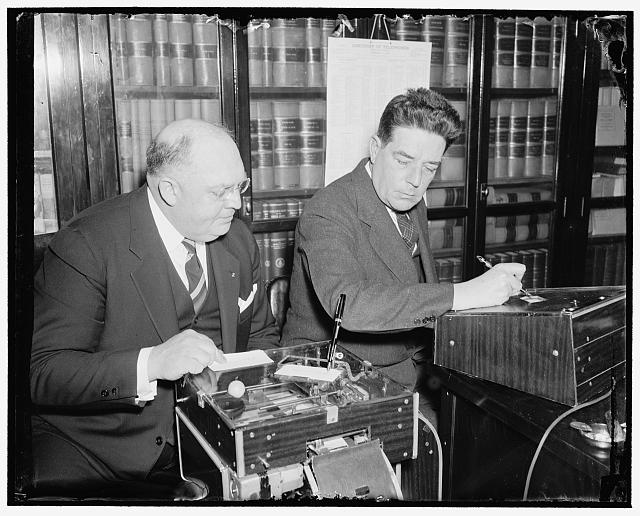 Demonstrates new signature machine to house member. Washington, D.C., March 18. The latest is the automatic electric signature machine invented by Glenn W. Watson, (left) who is shown in this picture demonstrating it to Rep. Lindsay C. Warren of North Carolina, 3/18/38