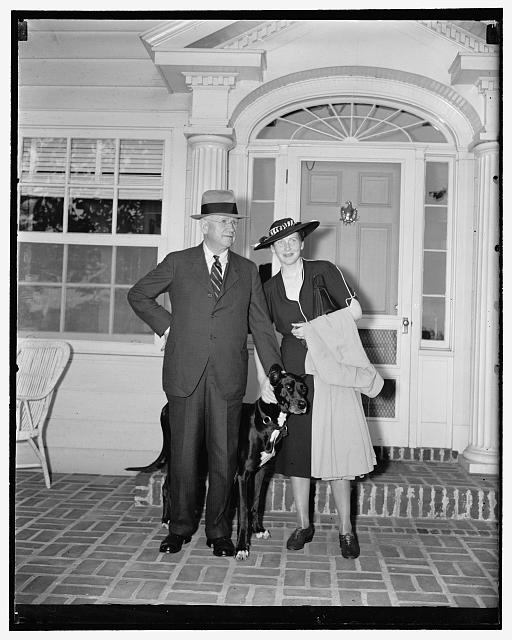 "Sec. Ickes and bride return from honeymoon. Washington, D.C., June 22. Returning from their European honeymoon to the Ickes country estate home near here today, Secretary on Interior Harold Ickes and his bride of a few weeks were greeted by ""Sooner,"" great dane pet of the Secretary, 6/22/38"
