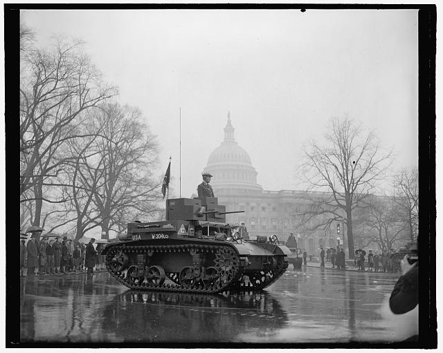 Latest types of tanks rumble past The Capitol in Annual Army Day Parade. Washington, D.C., April 6. Memories of the World War were revived today as the latest types of tanks, preceded by 20,00 soldiers and veterans, paraded past the U.S. Capitol in the Annual Army Day Parade which marked the 22nd anniversary of America into the World War. Thousands braved a heavy downpour to view the parade. 4-6-39