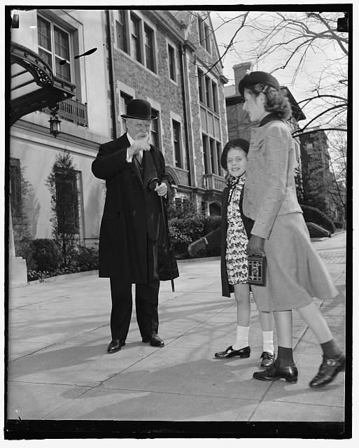 Chief Justice celebrates 77th birthday. Washington, D.C., April 11. Leaving his home for the usual morning stroll on his 77th birthday today Chief Justice Charles Evans Hughes acknowledges birthday greetings from Alice and Patricia Miller of Brooklyn, New York, who are spending the Easter Holidays in the Capitol. The Chief Justice appears fully recovered from his recent illness and is expected to resume his place on the bench when the high tribunal convenes again on April 17. 4-11-39