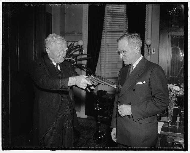 "Senatorial stickup. Washington, D.C., Feb. 17. After inspecting a couple of 45-caliber pistols formerly owned by Jesse James, famed bandit of another generation, Vice President Garner playfully tries his ""stickup"" technique on Senator Harry Truman of Missouri, present owner of the guns. Senator Truman secured the guns in Southern Missouri from a doctor's wife, whose husband received them in payment of medical services rendered Frank James, another of the James' boys. Jesse James had previously left them to Frank after he was killed by the pinkton men. The bandit garnered nearly $1,000,000 in a series of holdups with the guns, 2/17/38"