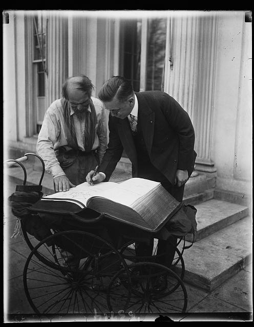 President Hoover's secretary signs famous autograph book. Secretary to the President Walter H. Newton signing the famous autograph book of Joseph Mikulee today at the White House. Mikulee, who hails from Jugoslavia, has toted this giant album around the world for the last five years and has recorded over 20,000 names of notables