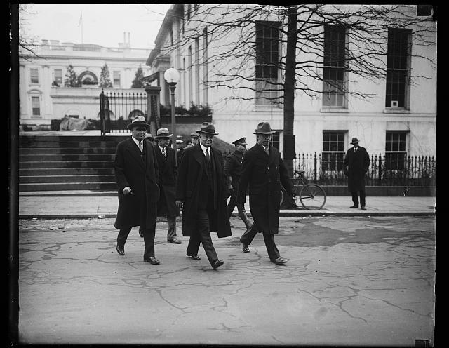 Off for the new offices. President Hoover (center) with Secretary George Akerson, (left) and Secretary Walter Hughes Newton (right). Secret Service men in the background. The picture was made as the President and his Secretaries left the White House for the temporary executive offices in the State, War, and Navy Department across the street. The old executive offices may be seen in the background