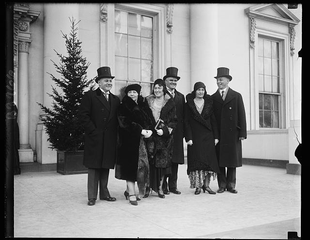 Executive Secretary Group. Secretaries to the president and their wives at the White House New Years Reception. In the group on the White House steps, left to right, are: Mr. Lawrence Richey, Mrs. Richey, Mrs. George Akerson, Mr. Akerson, Mrs. Newton and Mr. Newton