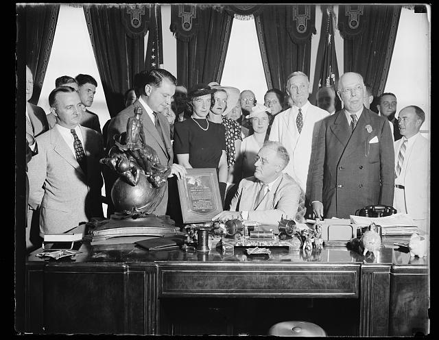 [Franklin D. Roosevelt at desk with group and the Collier Trophy]