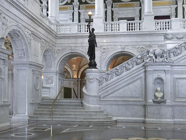[Great Hall. View of grand staircase and bronze statue of female figure on newel post holding a torch of electric light, with bust of Thomas Jefferson at right. Library of Congress Thomas Jefferson Building, Washington, D.C.]