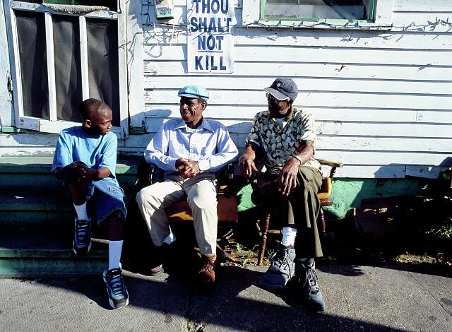 Friends relax in front of a home with a message, New Orleans, Louisiana