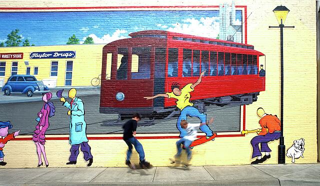 Actual skateboarders mimic those on a steet mural, Louisville, Kentucky