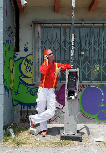 A very orange Bryan Jordan makes a call on his cell phone next to an empty phone booth, Melrose Avenue, Los Angeles, California