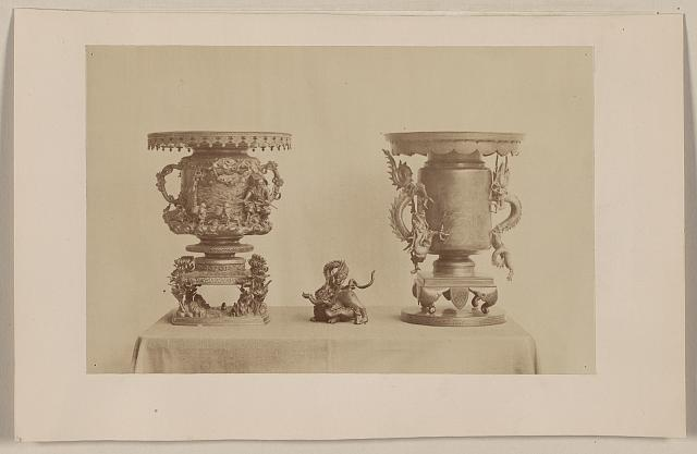 [Tall, metal, ornate plant stands and figurine, all with dragon motif, on a table]