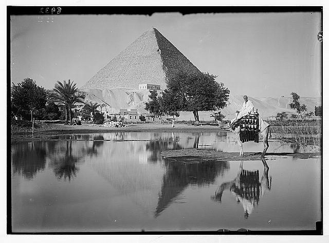 Egypt. Pyramids of Gizeh. The Great Pyramid. Reflecting pyramid &amp; mounted camelman