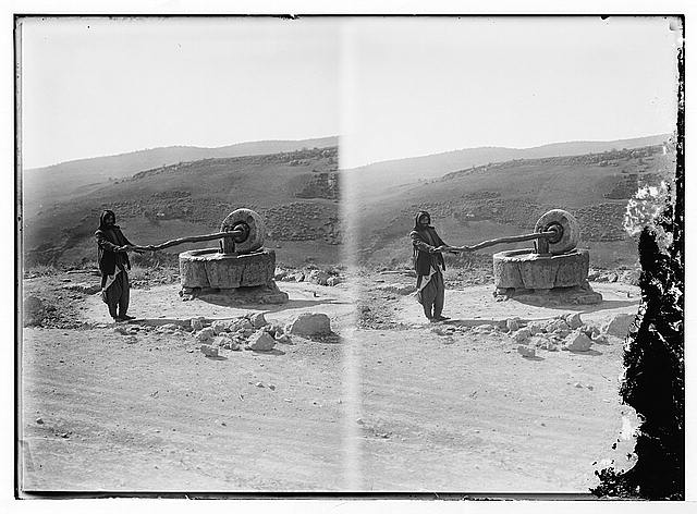 Bedouin man at a millstone
