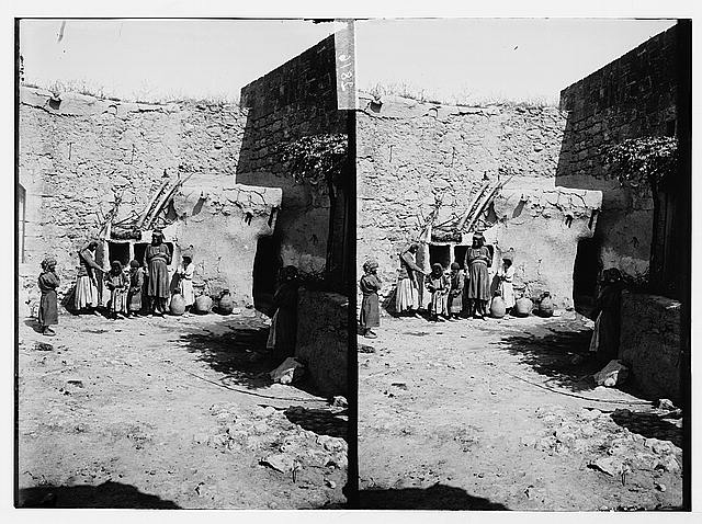[Woman and children in courtyard of house]