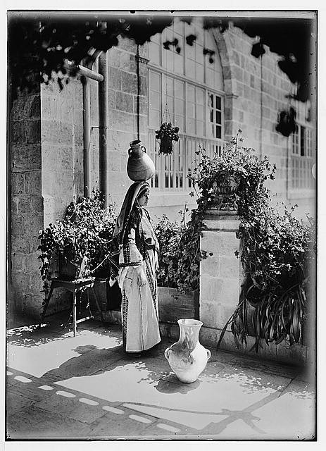 [Woman from Ramallah, standing in courtyard of the American Colony, with pottery vessel on her head]