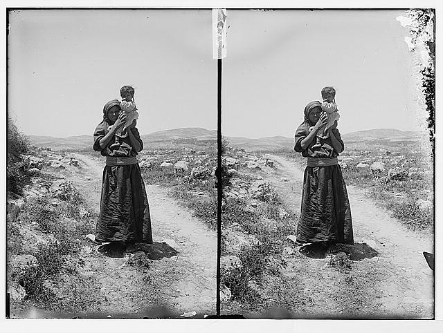 [Woman holding child, standing in road]