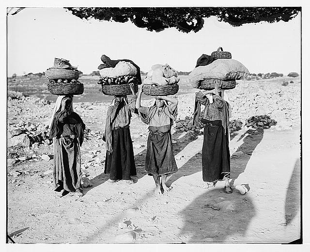Four Palestinian women on way to market with baskets on heads