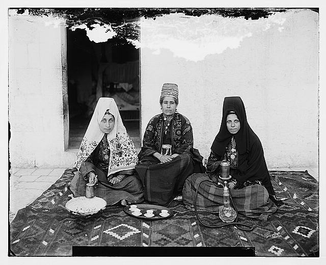 Three women seated on carpet, Bethlehem.