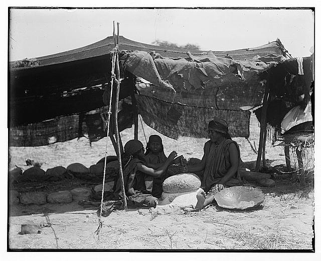 Bedouin women working primitive grainmill