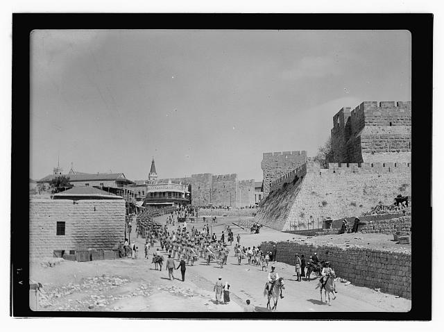 [People marching in a street in Jerusalem, near the city walls]