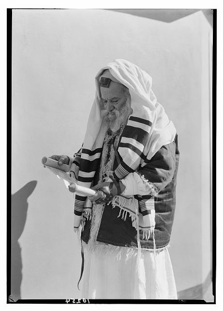Yemenite Rabbi Avram arrayed for prayer, reading scrolls