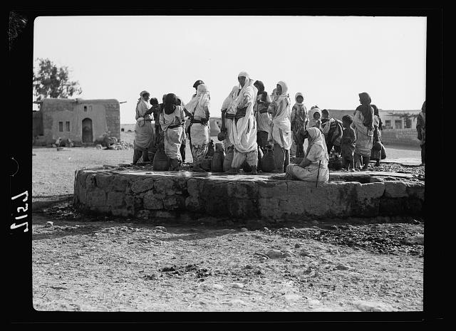 """At the well."" Crowds at [...] village well"