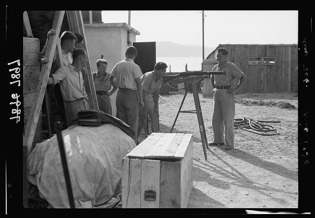 Ain Geb. Jewish settlement on the east side of S. Galilee. Group of settlers at the armoury [i.e., armory] inspecting rifles