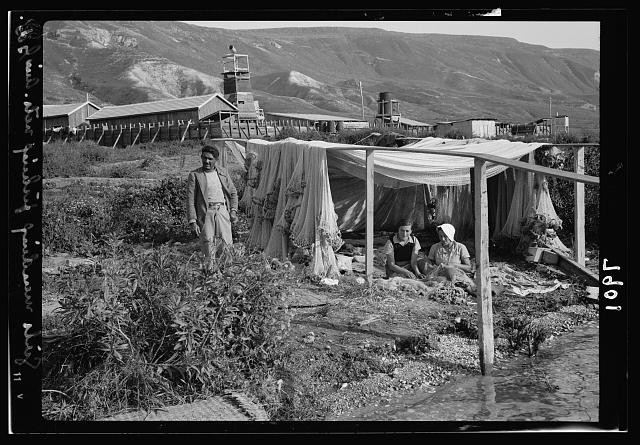 Ain Geb. Jewish settlement on the east side of S. Galilee. Girls of the settlement mending fishing nets. Colony in background