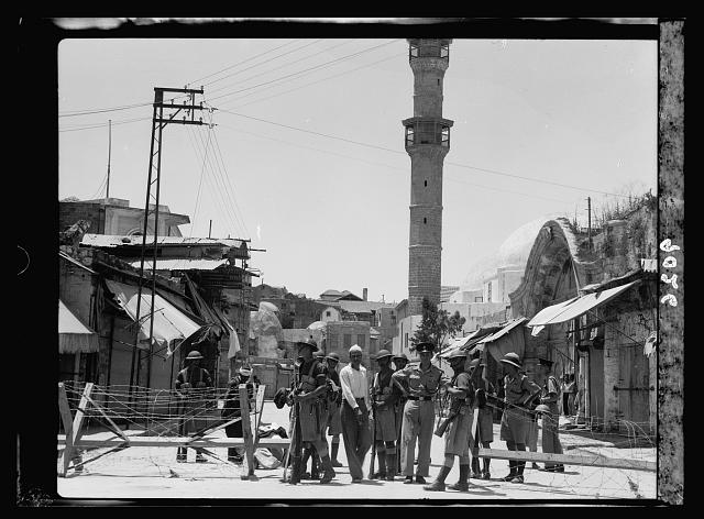 Palestine disturbances 1936. Jaffa. Troops & police guarding entrance to demolishing area