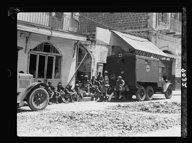 Palestine disturbances 1936. Jaffa. Troops & Red Cross ambulance on main street
